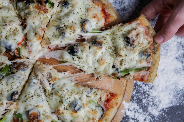 La pizza del primo piano su un supporto di legno, mano prende una fetta di orizzontale della pizza