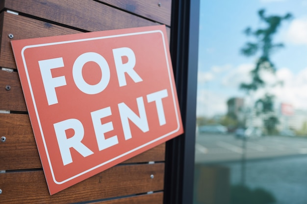 Close-up of placard for rent hanging on the door of modern office building
