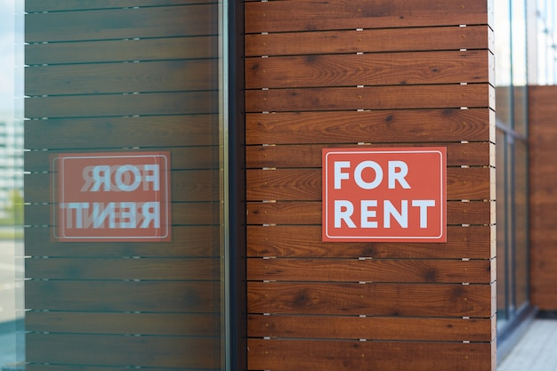 Close-up of placard for rent hanging on the wall of new office building