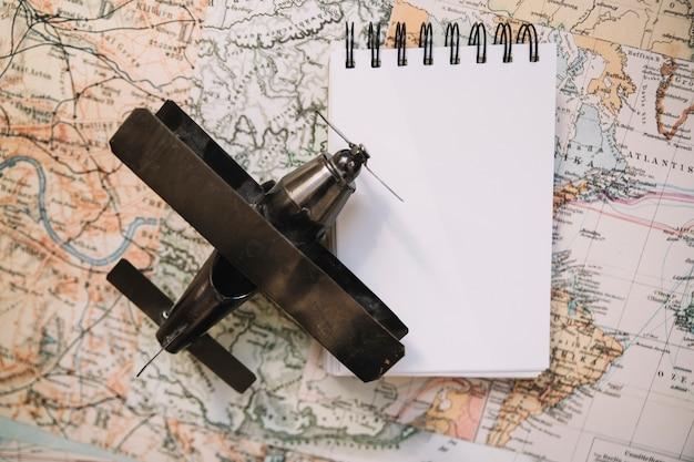 Крупный план самолета и блокнот на карте