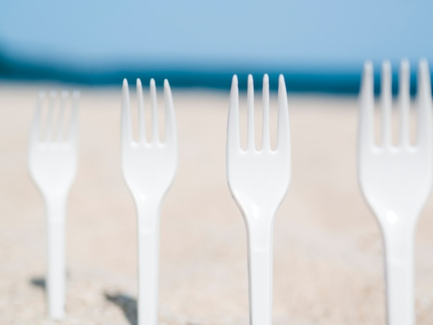Close-up of plastic forks stuck in sand on the beach