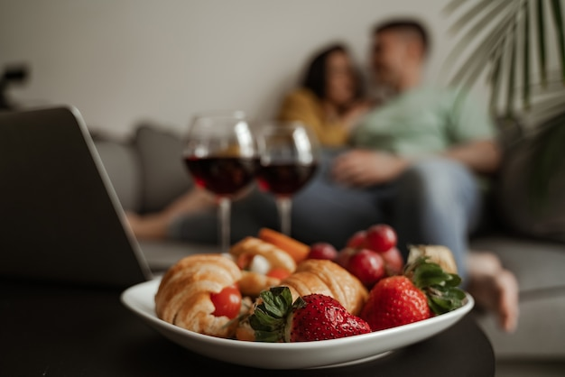 Close up plate of croissant and strawberry, lovely couple kissing with romantic feeling sitting on couch in living room. happy family moving to new apartment.