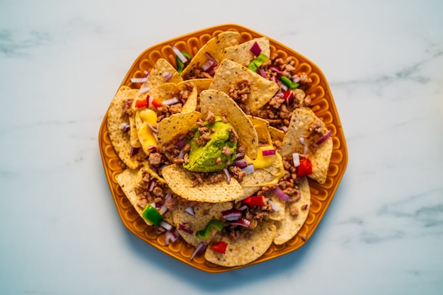 Close up of a plate of delicious tortilla nachos corn chips with melted cheese sauce, ground beef, jalapeno peppers, red onion, salsa, and sour cream with guacamole dip. top view