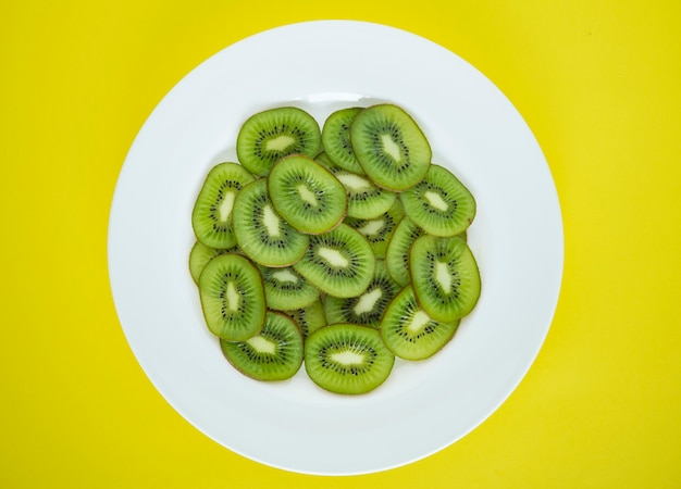 Close up of a plate of green kiwi fruit slices