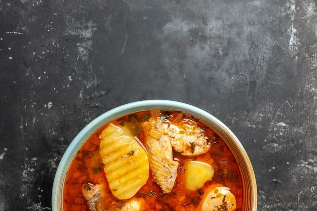Primo piano sul piatto con zuppa di pollo su sfondo nero