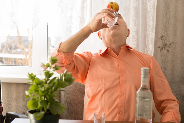 窓の近くのリビングエリアに座って、額にアップルと一緒に遊び心のある高齢者がウォッカワインを飲むのを閉じます。