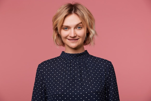 Close up of playful young beautiful attractive blonde woman dressed in blouse with polka dots, coquets, flirting, biting lip shows attraction, isolated