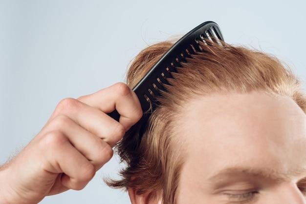Закройте порадовал рыжеволосый мужчина, расчесывает волосы расческой.