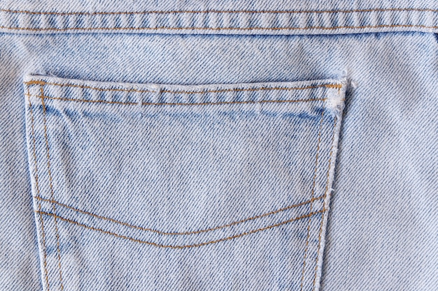 Close up of pocket on denim trousers with tear and old, detail jeans texture background.
