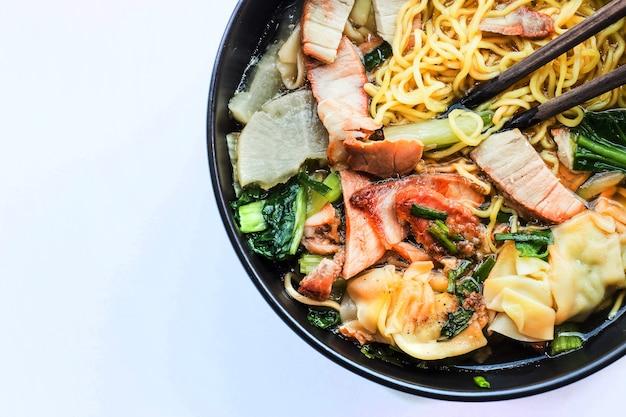 白い表面に木の箸で中華麺の豚肉と野菜をクローズアップ