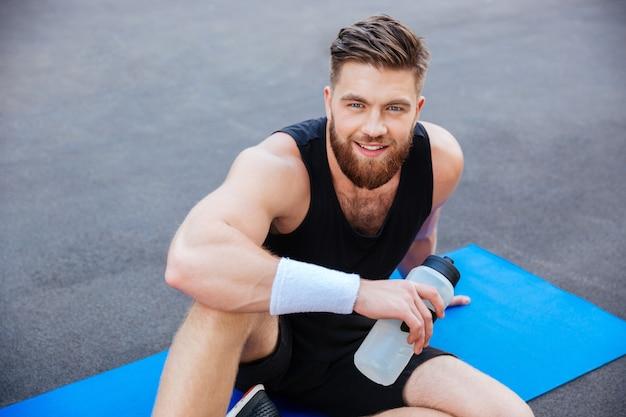 야외에서 앉아서 휴식을 취하는 물 한 병을 들고 웃고 있는 젊은 스포츠맨의 초상화를 닫습니다