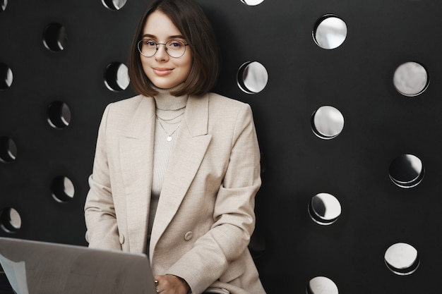 젊은 우아한 여자, 대학생 인터넷에서 경력 기회를 검색, 바닥에 공동 작업 공간에서 공부로 무릎에 컴퓨터를 들고 카메라 미소의 근접 porrait.