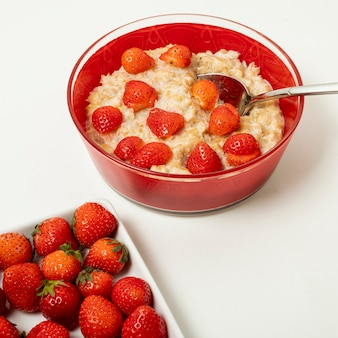 Close up porridge with strawberries arrangement on plain background