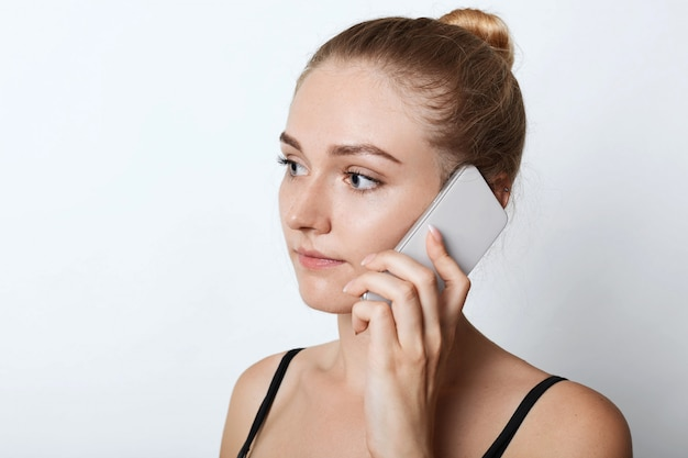 Close up portait of blonde female looking aside with serious expression while calling his friend or relatives, listening attentively something. young attractive female chatting over mobile phone.