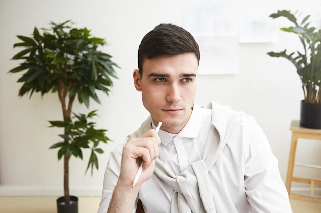 Close up portait of handsome clean shaven young european male designer having pensive look while working at his workplace, thinking of new ideas and solutions. people, job, talent and creativity