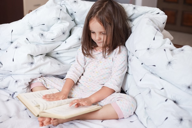 Close up portait of little girl sittng in bed, wearing pajama, charming female kid with dark hair, holding bookin hand and reading it, child looking at her book, reads interestin fairy tale.