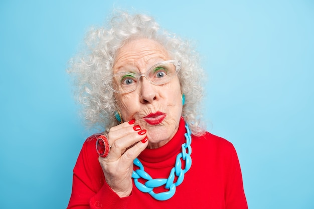 Close up portait of lovely wrinkled grey haired woman keeps red painted lips folded looks with romantic expression directly, wears optical glasses and casual jumper with necklace