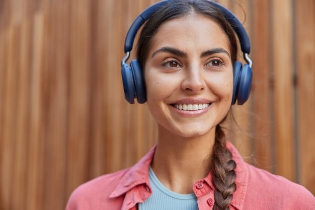 賢い女子学生のクローズアップは、ワイヤレスヘッドホンでスピーカーが発音した外国語を学び、正しい発音を覚えようとすることで、リスニング体験の笑顔が楽しくなります。