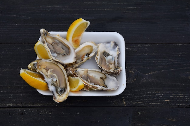 Close up portion of fresh open raw juicy oysters with lemon wedges on white plastic tray over black wooden table with copy space, high angle view