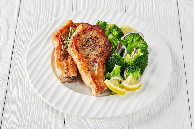 Close-up of a portion of fried pork rib chops with lemon wedges, broccoli salad on a white plate on a wooden table