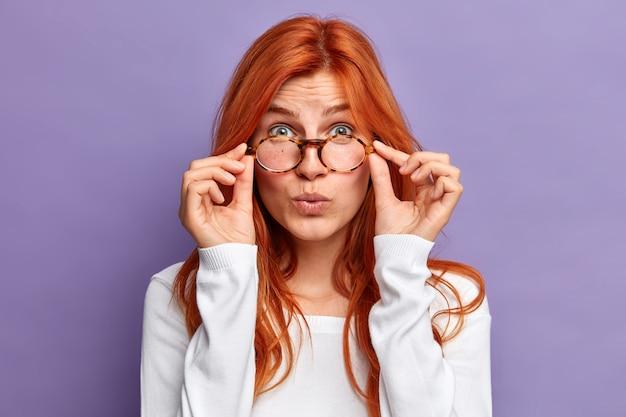 Primo piano portrai di donna rossa sorpresa tiene le mani sul bordo degli occhiali guarda con meraviglia sente notizie sorprendenti indossa un maglione a maniche lunghe bianco.