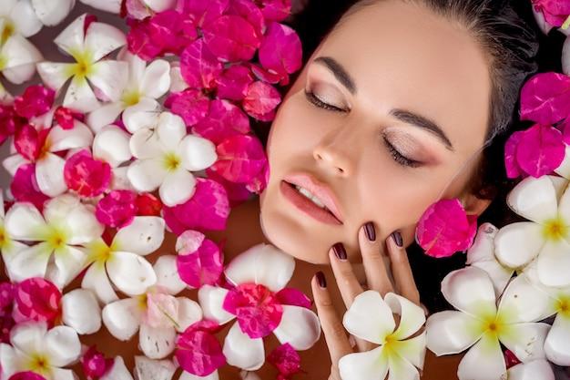 クローズアップの肖像画目を閉じた魅力的なブルネットは、花びらの間のお風呂でリラックスします。