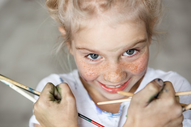 Close up portrait of adorable blonde little female child in white t-shirt holding brushes, having fun, enjoying drawing with happy expression