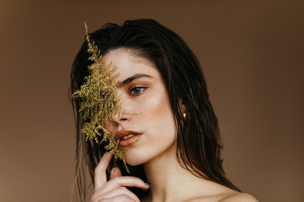 Close-up portrait of adorable brunette girl with plant.  amazing female model holding green leaf.