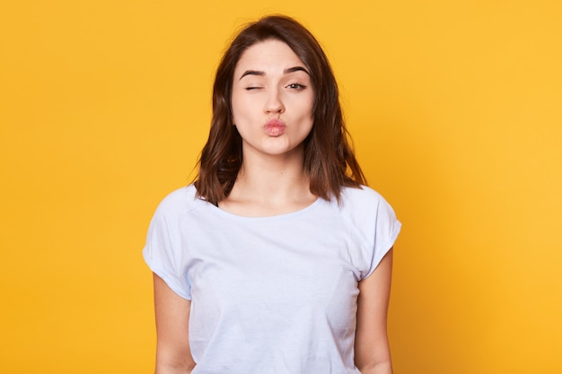 Close up portrait of adorable brunette woman pouts lips and winks, makes grimace, rounds lips for making kiss