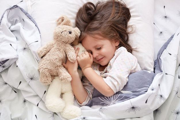 Close up portrait of adorable dark haired little girl calmly sleeping with sweet golden retriever pet in bedroom