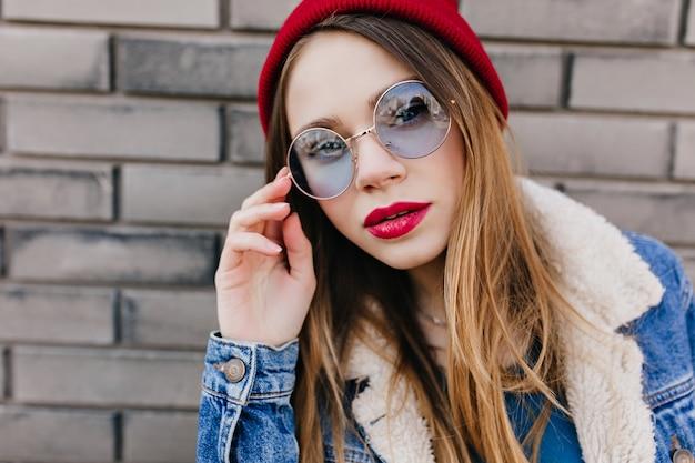 Ritratto del primo piano della ragazza adorabile con trucco luminoso con l'espressione seria del viso. foto all'aperto di spettacolare signora in cappello e giacca casual in piedi sul muro di mattoni.