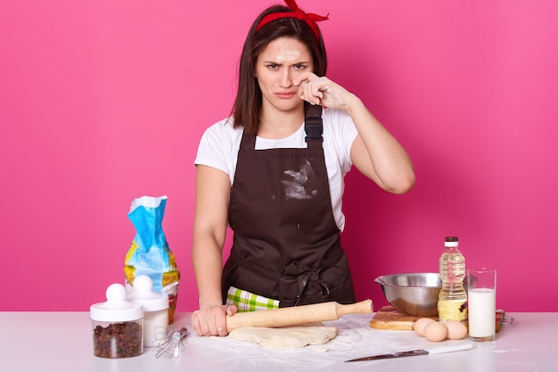 Close up portrait of adorable housewife or baker looks tired and sad, spends lots hours in kitchen, has dirty face with flour, holds baking rolling pin and rolls out dough isolated on pink wall.