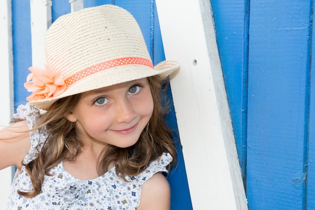 Close-up portrait of adorable smiling child girl wearing straw flowers hat