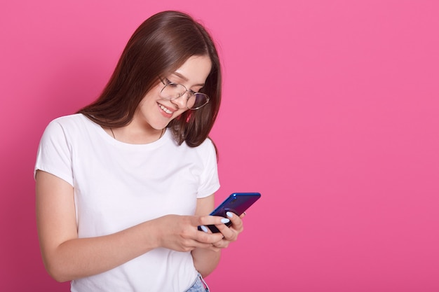 Close up portrait of adorable woman typing message to her friends or husbaund. young female holding mobile phone
