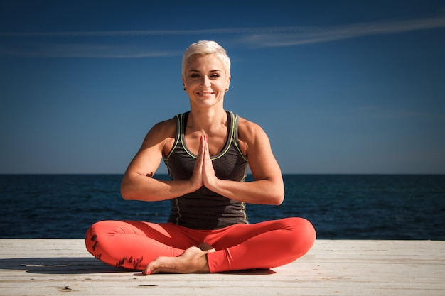 Close-up portrait of adult blond woman with short haircut practices yoga on the pier against the background of the sea and blue sky
