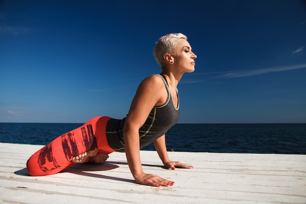 Close-up portrait of adult blond woman with short haircut practices yoga