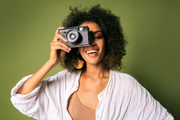 Close up portrait of afican woman holding retro photo camera and laughing.