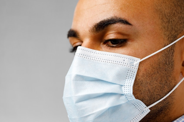 Close up portrait of african american male wearing medical mask against grey background