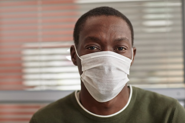 Close up portrait of african-american man wearing mask and looking at camera against office blinds background, copy space