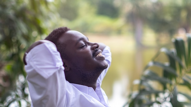 Close up portrait of african business man with calm face close eyes stand in green nature with hands above head