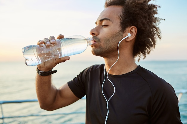 Close up portrait of afro-american fit athlete drinking water out of plastic bottle with earphones on. refreshing himself with water and wearing black t-shirt