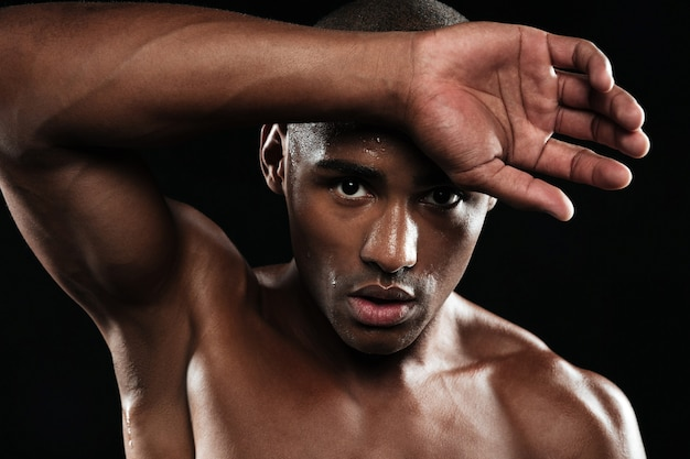 Close-up portrait of afro american sports man, resting after workout, wipes sweat from his forehead