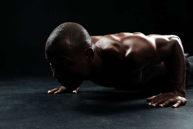 Close-up portrait of afro american sports man, with beautiful muscular body doing pushup exercise on floor