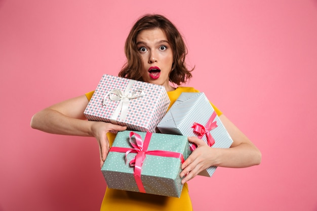 Close-up portrait of amazed beautiful woman holding bunch of presents,
