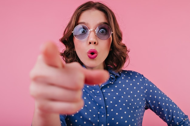 Close-up ritratto di stupita donna dai capelli corti indossa occhiali blu. giovane donna in camicia elegante che esprime emozioni sorprese sulla parete rosa.