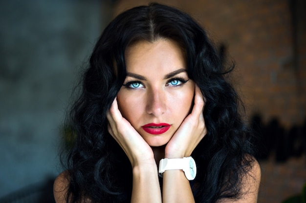 Close up portrait of amazing beauty woman with fluffy brunette hairs and big blue yes looking straight, wearing white watch and bright make up.