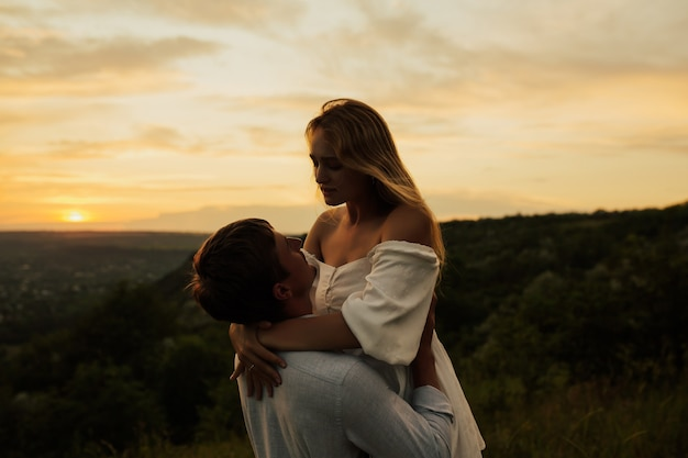 Close up portrait of amazing couple embracing against sunset while dating.