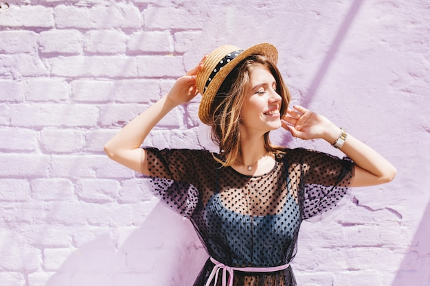 Close-up portrait of amazing laughing girl in straw hat with ribbon in summer day