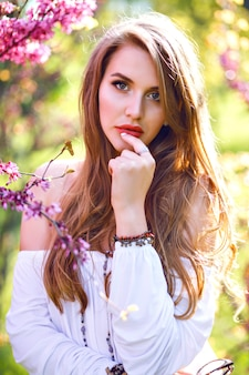Close up portrait of amazing magazine tender woman with natural long hairs and perfect skin posing at blooming garden, spring time.