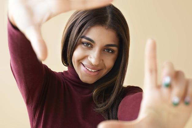 Close up ritratto di incredibile bella donna di razza mista sorridendo felicemente e gesticolando, facendo cornice con le dita, guardando attraverso di essa come se si stesse scattando una foto. messa a fuoco selettiva sul viso della ragazza